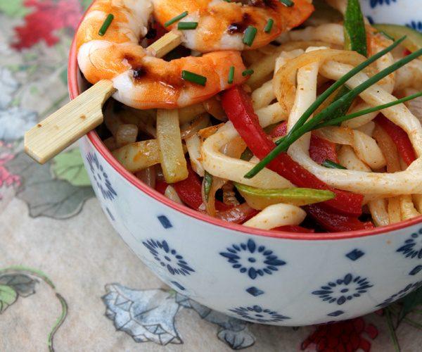 Udon sautées aux légumes et brochettes de crevettes